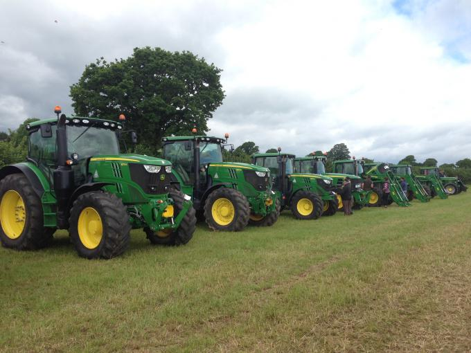 Green tractors lined up for sale at a Kivells machinery sale in a field