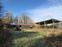 Kivells amenity land at Lesnewth for sale. Green field with outbuildings and trees with a blue sky