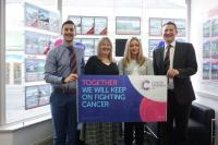 Staff members Sam, Mandy, Katie and Dan, inside Kivells Bude office holding a Cancer Research UK Banner