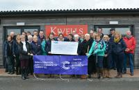 Staff at Kivells Holsworthy Livestock Market presenting the cheque for £2,500 to Mary Bromell, Treasurer of the Bude and Stratton Cancer Research UK Committee