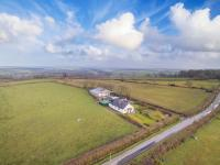 Kivells Fairview aerial photo of farm and land with blue sky and white clouds above it