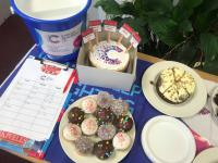 Cakes displayed in Kivells Launceston office with collection bucket for Cancer Research UK