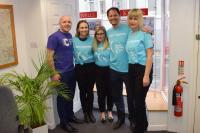 Kivells Liskeard staff Sam Turner, Rebecca Peace, Claire Whiting, Richard Luscombe and Jane Heard standing side by side in the Liskeard office in CRUK Relay For Life t-shirts