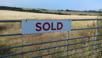 Sold sign on the gate of Land at Cranford with arable land and fields leading to the distance with blue sky