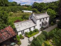Aerial shot of Minehouse Farm, Herodsfoot showing the white walled property with grey slate roof, outbuilding and surrounding gardens and orchard