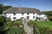 Outside front image of Wallon Farm Cottage, a white thatched cottage with garden