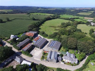 Aerial view of Helland Barton Farm with agricultural buildings, farmhouse and land