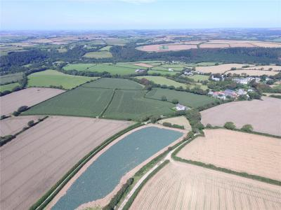 Panoramic view of Helland Barton Farm with agricultural buildings, farmhouse and land