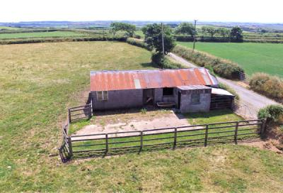 Aerial shot of metal agricultural buildings and green land, part of Jenns Farm Bradworthy for sale with Kivells
