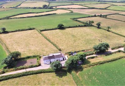 Aerial shot of Jenns Farm Bradworthy, farmouse, agricultural buildings and land for sale with Kivells