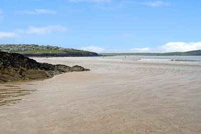 Kivells New Polzeath and Pentireglaze Beach - Sand with blue sky and sea with surfers with properties in background on land