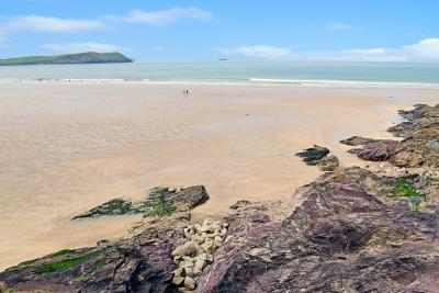 Kivells New Polzeath and Pentireglaze Beach - Sand and rocks with blue sky and sea with surfers
