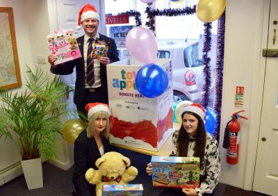 Kivells staff in Christmas hats holding toys in front of the Pirate FM Toy Appeal collection box in the Kivells Liskeard office