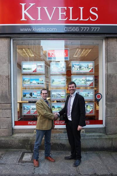 Kivells Tom Rattray and David Turnbull shaking hands outside the Kivells Launceston office