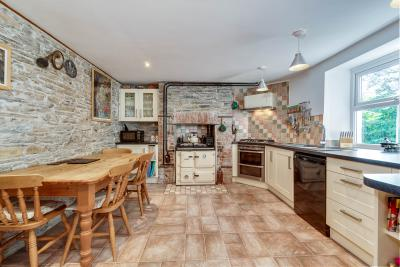 Minehouse Farm, Herodsfoot Kitchen with stone walls, pine table and chairs, brown tiled floors, fitted units and rayburn